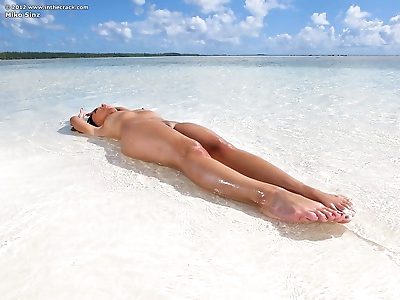 Swimsuit clad Miko Sinz reefing nether region apart for men to see on beach