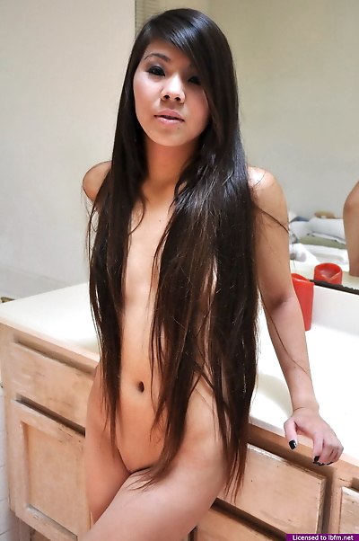 Young Asian girl with long hair that touches her ass shows her tight slit